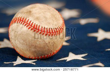 Old and weathered baseball on American flag
