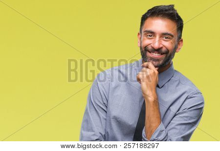 Adult hispanic business man over isolated background looking confident at the camera with smile with crossed arms and hand raised on chin. Thinking positive.