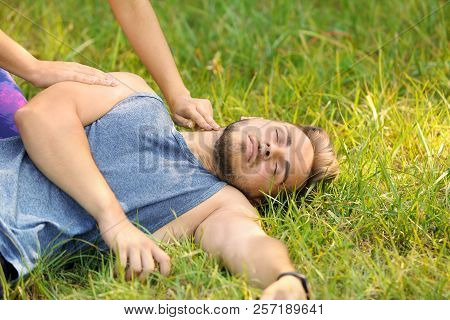 Woman Checking Pulse Of Unconscious Man Outdoors