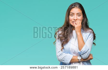 Young beautiful arab woman over isolated background looking stressed and nervous with hands on mouth biting nails. Anxiety problem.