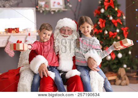 Little Children With Gift Boxes Sitting On Authentic Santa Claus' Knees Indoors