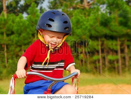 Cute toddler wearing helmet riding tricycle