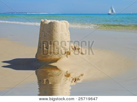 Pretty sand castle by tidepool with sailboat on ocean in distance