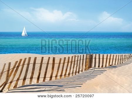 Sailboat on pretty sea with sand dune fence in foreground