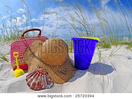 Straw beach bag and hat by sand toys on dune