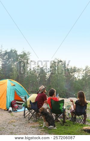 People Resting Near Camping Tent In Wilderness