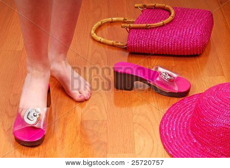 Young girl surrounded by pink fashion accessories