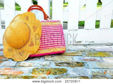 Summer purse and hat by white picket fence gate and old brick pavers