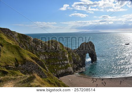 Blue Sky And White Clouds, The Waves Under The Steep Cliffs Continue To Surf On The Beach, And There
