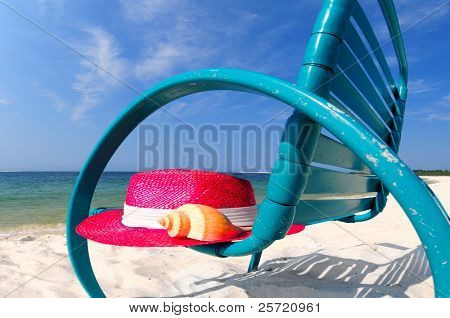 Pretty beach chair with hat and shell at seashore
