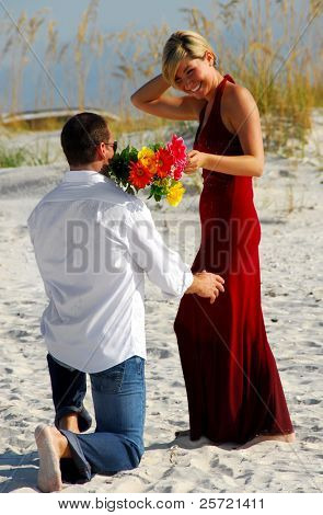 Man down on one knee offering bouquet to woman