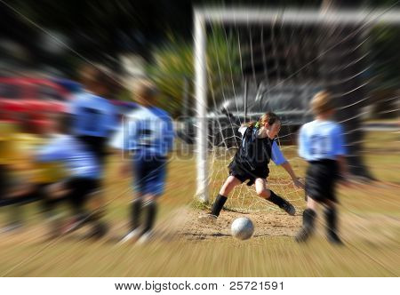 Young kids playing soccer on community field