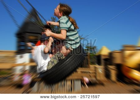 Young kids having fun on tire swing poster