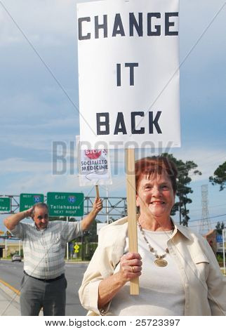 PENSACOLA, FLORIDA - SEPTEMBER 7: Concerned citizens hold signs to protest Healthcare Reform while standing along Davis Highway on September 7, 2009 in Pensacola, Florida.