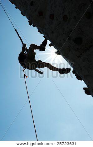 Man on steep climbing wall against blue sky