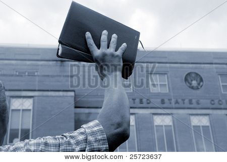 Man holding up bible in front of court house