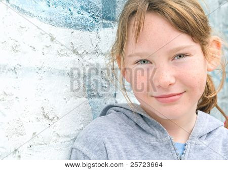 Cute young girl leaning on urban wall