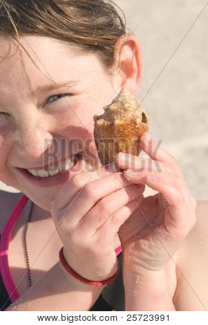 Young girl excited to find pretty seashell