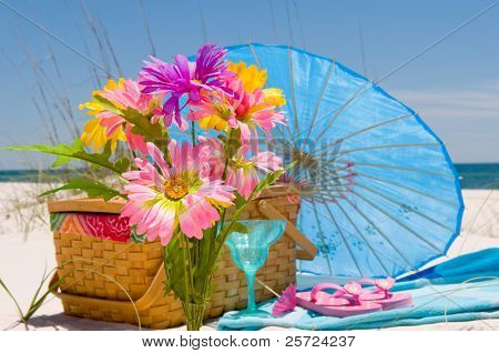 Pretty flowers at picnic on beach