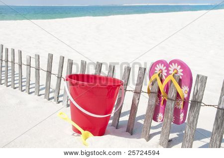 colorful sand toy and flip flops on beach