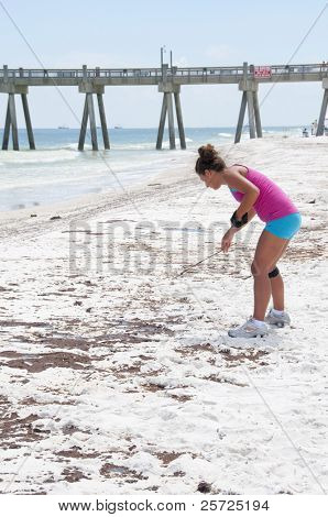 PENSACOLA BEACH - JUNE 23: An unidentifed beach goer looks at oil patches on June 23, 2010 in Pensacola Beach, FL.