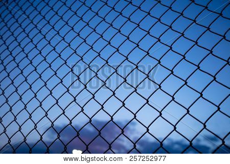 Dark blue sky through wire mesh fence. Blur background, close up view of link cage, wallpaper.