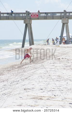 PENSACOLA BEACH - JUNE 23:  A beachgoer steps over oil patches on June 23, 2010 in Pensacola Beach, FL. BP oil workers attempt to clean the beach area in the background.