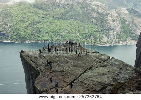 View Of Preikestolen Cliff With Silhouettes Of People On A Foggy Rainy Day. Lysefjorden Fjord In Nor