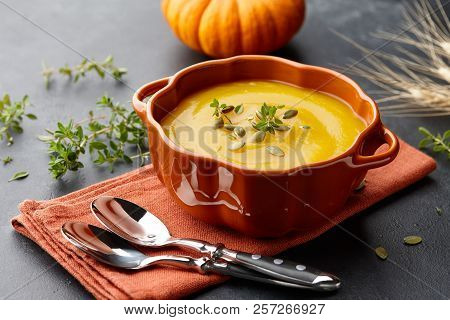 Pumpkin Soup With Thyme Herb, Cream And Pumpkin Seeds Served In Orange Pumpkin Shaped Bowl
