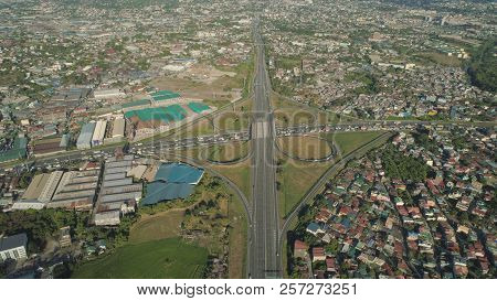 Aerial view of highway with road junction, car and traffic in Manila, Philippines. Highway in Manila among residential buildings. View of highway intersection. poster