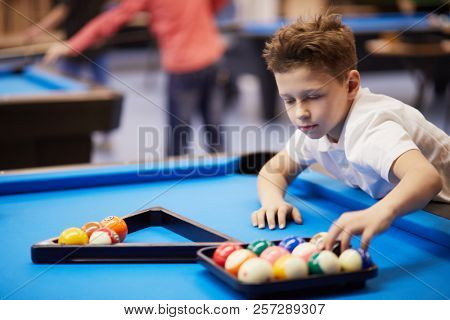 Boy moves pool balls from tray to triangle rack on billiard table, focus on spa?e inside rack.