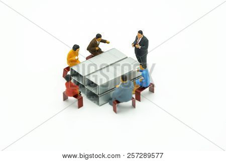 Miniature People Sitting On Red Staples Placed White Background. Meeting Or Discussion Using As Back