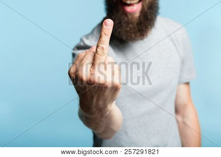 bearded man showing middle finger. provocation defiance attitude and offensive rude behavior concept. cropped shot of a male torso on blue background. casual hipster in grey t-shirt. poster