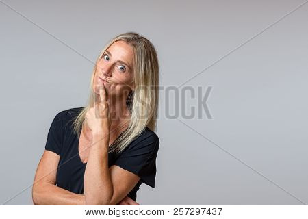 Speculative Woman Looking At The Camera With Wide Eyed Thoughtful Expression With Her Head Tilted To