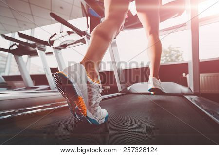 Close Up Womans Legs Running At The Treadmill In The Gym Against The Sunrise. Lady Wearing White Ora