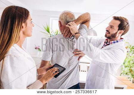 Man Having Chiropractic Arm Adjustment. Physiotherapy, Sport Injury Rehabilitation. Senior Man Exerc