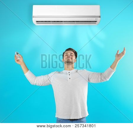 Young Man Operating Air Conditioner On Color Background