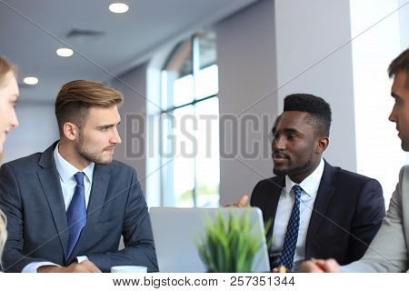 Business People In Discussing Something While Sitting Together At The Table.