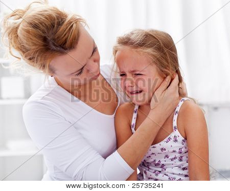 Mother comforting her crying little girl - parenthood concept