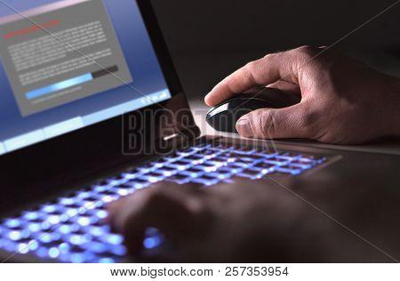 Man Installing Software In Laptop In Dark At Night. Hacker Loading Illegal Program Or Guy Downloadin