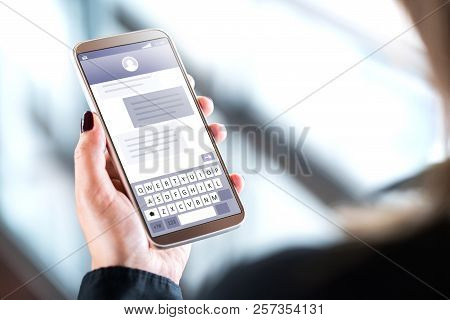 Woman Sending Text Messages With Mobile Phone. Cellphone In Hand With Sms Application On Screen. Per