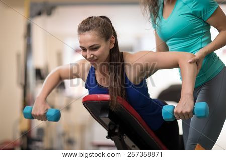 Personal Trainer Helping Pretty Woman With Weight Training Equipment In Gym
