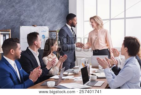 Group Of Cheerful Business People Sitting At Meeting While Boss And Man Shaking Hands