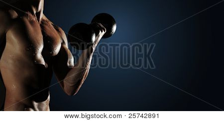 Part of a wet man's body with metal dumbbell on a dark background