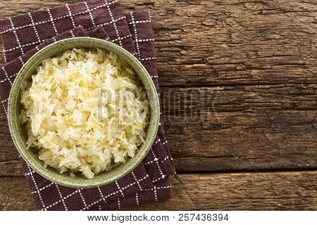 Fresh Healthy Sauerkraut In Bowl, Photographed Overhead On Rustic Wood With Copy Space On The Side (