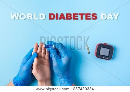 Inscription World Diabetes Day, Nurse Making A Blood Test With Lancet. Man's Hand With Red Blood Dro