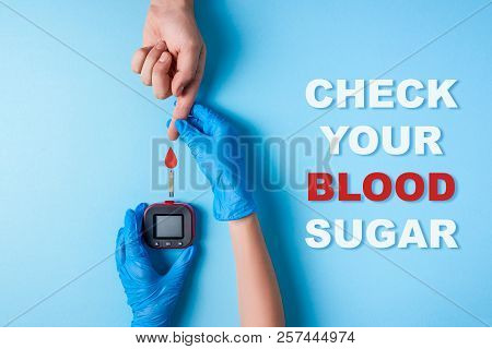 Inscription Check Your Blood Sugar And Nurse Making A Blood Test. Man's Hand With Red Blood Drop And