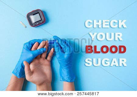 Inscription Check Your Blood Sugar, Nurse Making A Blood Test With Lancet. Man's Hand, Red Blood Dro