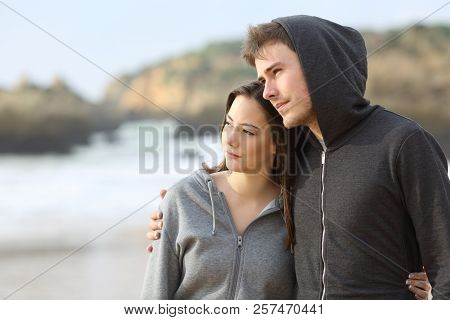 Couple Of Melancholic Teens Contemplating Ocean Walking On The Beach