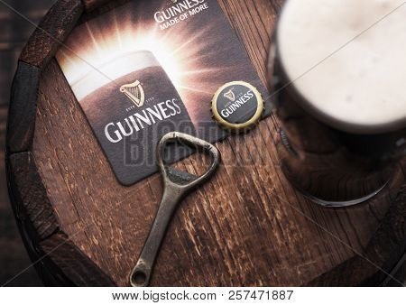 London, Uk - April 27, 2018: Original Glass Of Guinness Draught Stout Beer On Top Of Old Wooden Barr